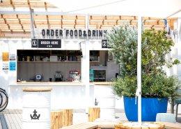 海沿いに立つおしゃれなオープンBBQレストランをコンテナハウスのバー