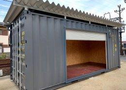 自宅敷地内にガレージ感のある屋根付きのコンテナ倉庫のシャッターの様子
