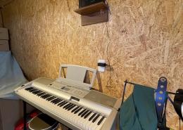 趣味と実益を兼ねたウッドデッキ付きコンテナハウスルーム キーボードとスピーカー